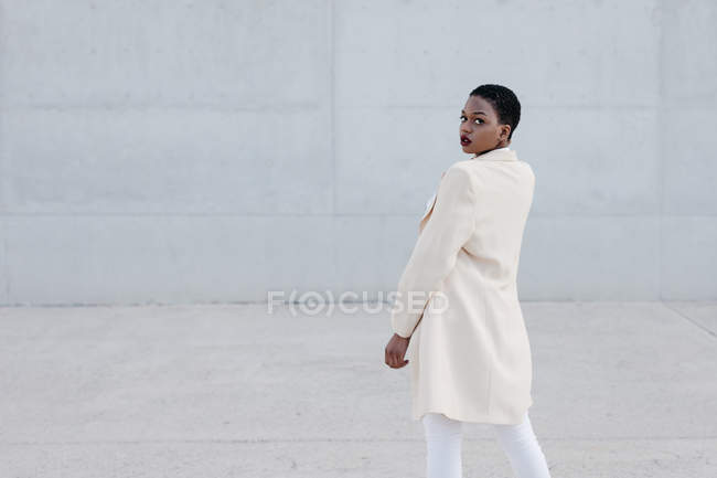 Fashion short haired ethnic woman model in white trousers and coat posing against grey wall — Stock Photo
