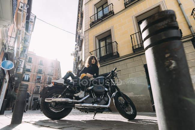 Mujer joven en moto personalizada - foto de stock