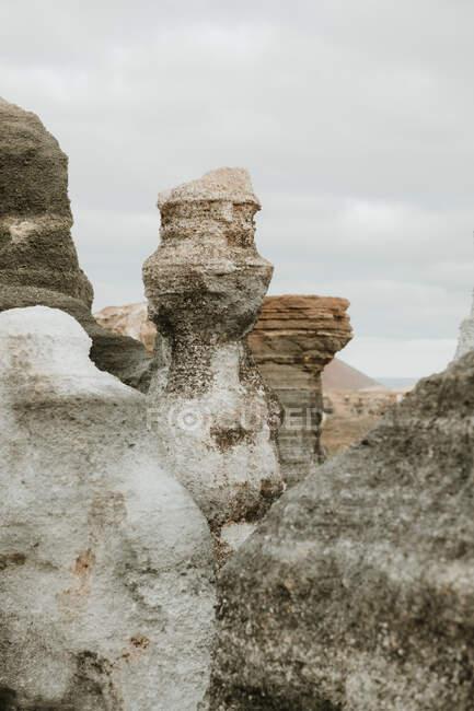 Gray overcast sky over amazing rough stone pillars in wonderful countryside — стокове фото