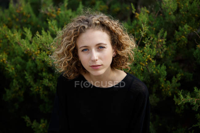Portrait of young charming woman with blonde curly hair looking at camera in nature — Stock Photo