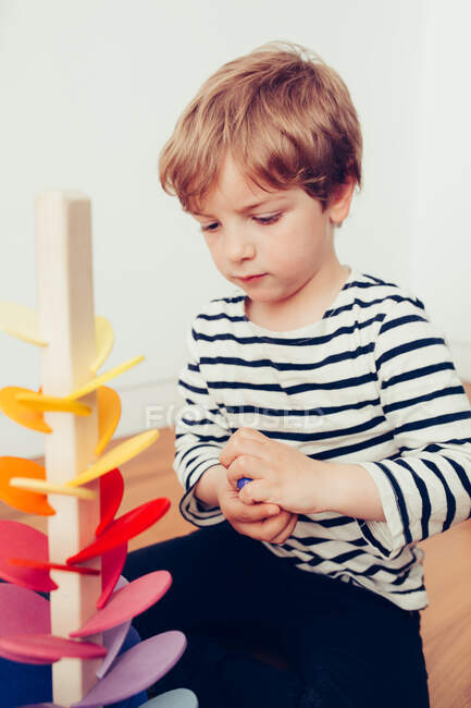 Blonde cute boy playing with waldorf sounding tower with marbles — Stockfoto
