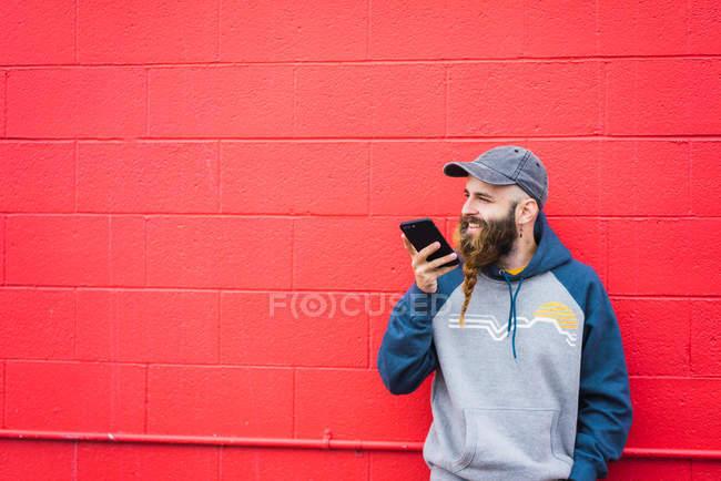 Attraente ragazzo con la barba intrecciata che parla su smartphone mentre si appoggia muro rosso sulla strada della città — Foto stock