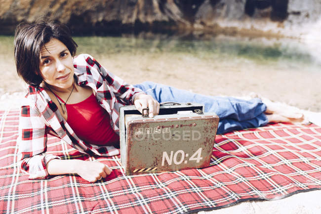Smiling adult woman lying on plaid on lake shore in cliffs holding old rusty case with provision smiling at camera — Stock Photo