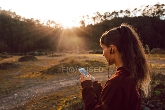 Young hipster woman with piercing and earphones listening music with mobile phone in countryside — Stock Photo
