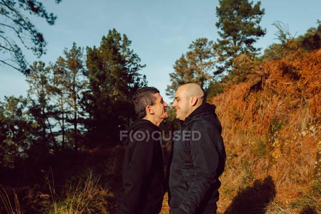 Гомосексуальная пара, стоящая лицом к лицу в лесу в солнечный день — стоковое фото