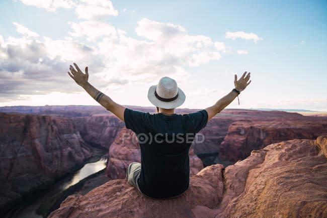 Обратный вид человека, протягивающего руки и любующегося видом величественного каньона на облачно-голубое небо на западном побережье США — стоковое фото
