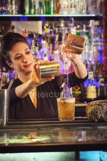 Attractive woman pouring various liquids in glass while preparing cocktail behind counter in bar — Stock Photo