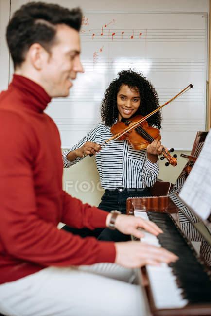 Seitenansicht eines jungen Mannes, der neben einer schwarzen Frau Klavier spielt und im Musikstudio Geige spielt — Stockfoto