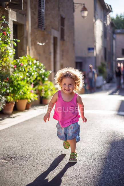 Happy funny girl running on asphalt street between buildings in summer — стоковое фото