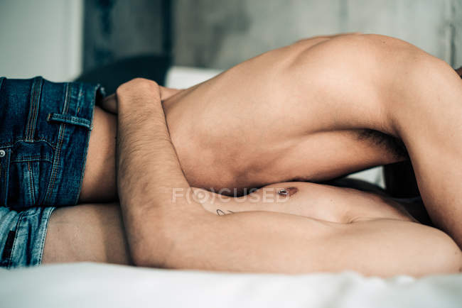 Cropped image of passionate sexual happy shirtless gay couple in an intimate moment in the bed at home — Stock Photo