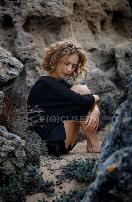 Giovane donna premurosa seduta in rocce e abbracciare le ginocchia — Foto stock