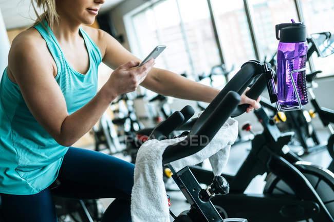 Женщина со смартфоном, полотенцем и водой в тренажерном зале — стоковое фото