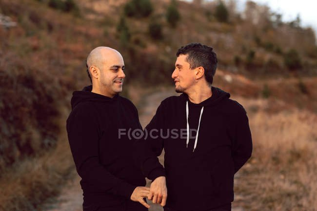 Romantic homosexual couple walking on path in nature — Stock Photo