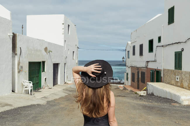 Back view of stylish woman touching hat while standing on shabby street of small coastal town on cloudy day near sea — стокове фото