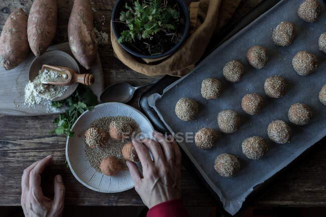 Людина, яка котиться в хлібних крихтах солодка картопля. — стокове фото
