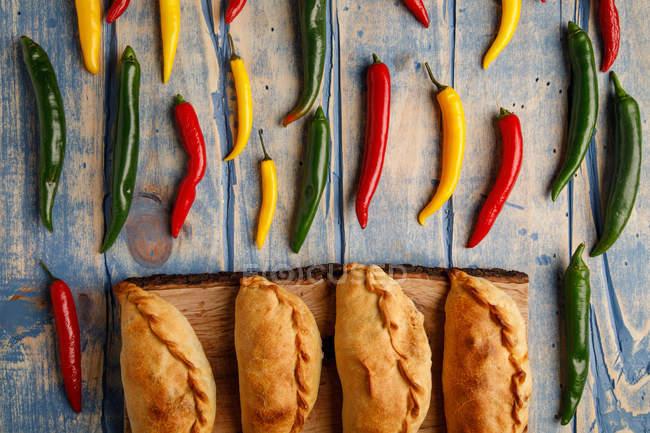 Rissóis cozidos caseiros e pimentas de pimentão verdes e vermelhas frescas na tabela de madeira cinzenta — Fotografia de Stock