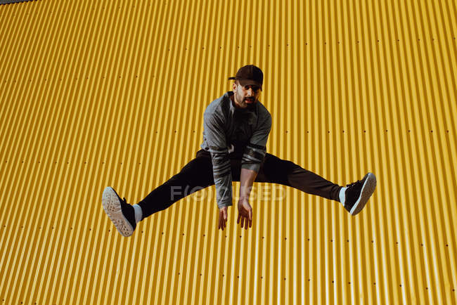 Barbu gars en tenue à la mode bondissant vers le haut et regardant la caméra contre le mur jaune du bâtiment moderne par jour ensoleillé — Photo de stock