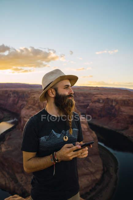 Hombre guapo con teléfono móvil mientras está de pie contra el magnífico cañón y el río durante el atardecer en la costa oeste de EE.UU. - foto de stock
