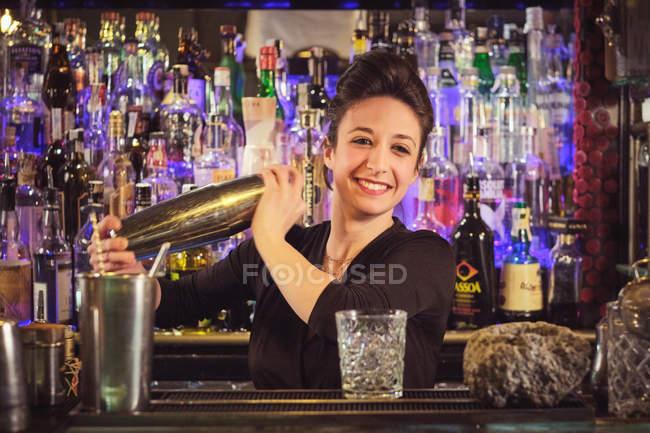 Cheerful barman shaking cocktail — Stock Photo