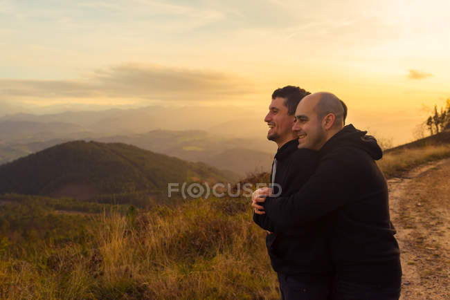 Happy homosexual couple embracing and enjoying sunset on route in mountains — Stock Photo