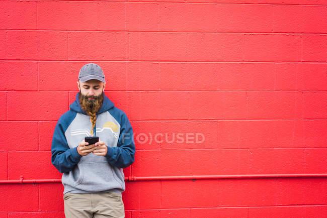 Attrayant gars avec barbe tressée navigation smartphone tout en se penchant mur rouge sur la rue de la ville — Photo de stock