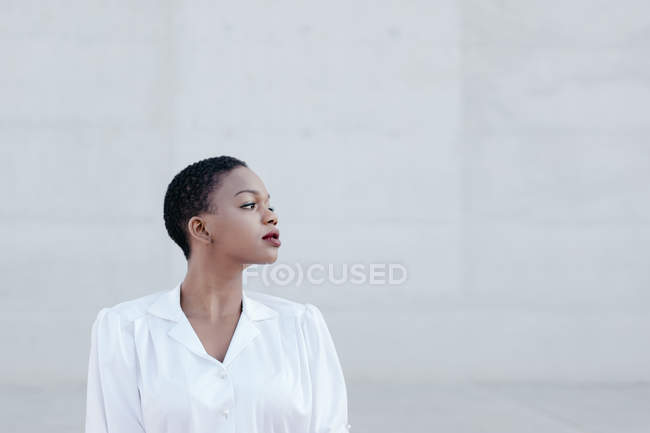 Профиль чувственной женщины с короткими волосами, позирующей против серой стены — стоковое фото