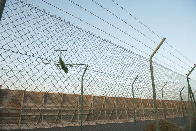 Современные самолеты летят против безоблачного голубого неба за забором безопасности в аэропорту — стоковое фото