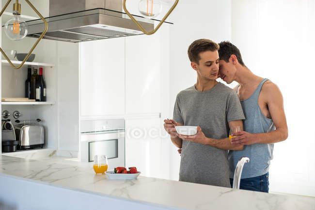 Affectueux couple gay avoir un petit déjeuner sain et câlins à la maison dans la cuisine — Photo de stock