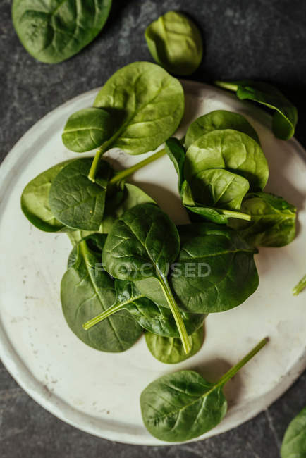 Свіже листя шпинату на білій пластині на сірій поверхні — стокове фото