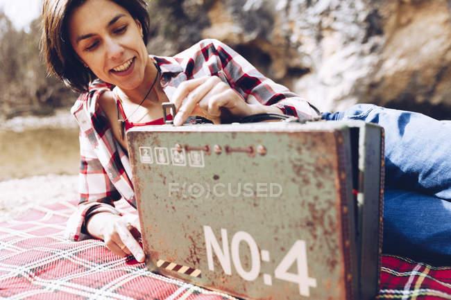 Mujer adulta sonriente acostada sobre cuadros en la orilla del lago en acantilados que sostienen un viejo caso oxidado con provisión sonriendo a la cámara - foto de stock