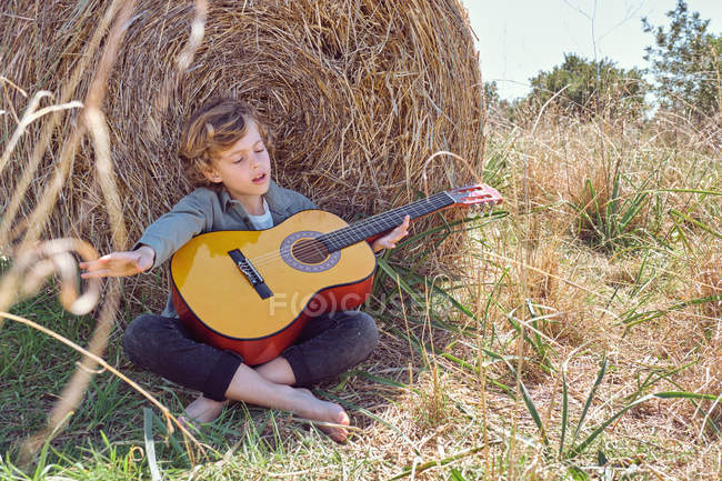 Netter Junge mit geschlossenen Augen, der Akustikgitarre spielt und singt, während er an einem sonnigen Tag auf dem Land in der Nähe einer riesigen Rolle trockenem Heu sitzt — Stockfoto