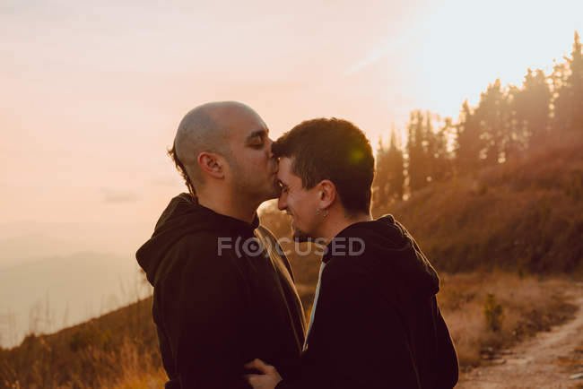 Happy homosexual couple hugging and kissing on path in forest in sunny day — Stock Photo