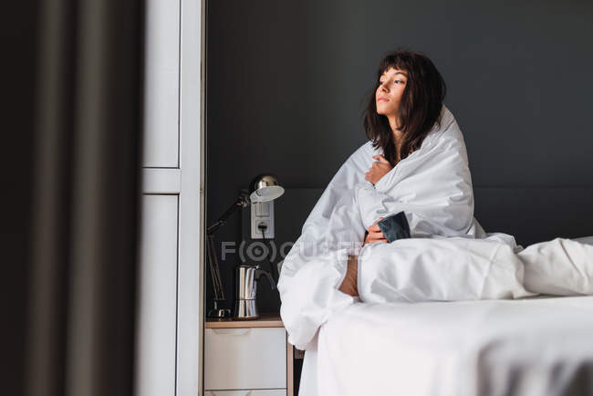 Young dozy woman with mug of drink covered in duvet sitting on bed in bedroom — Stock Photo