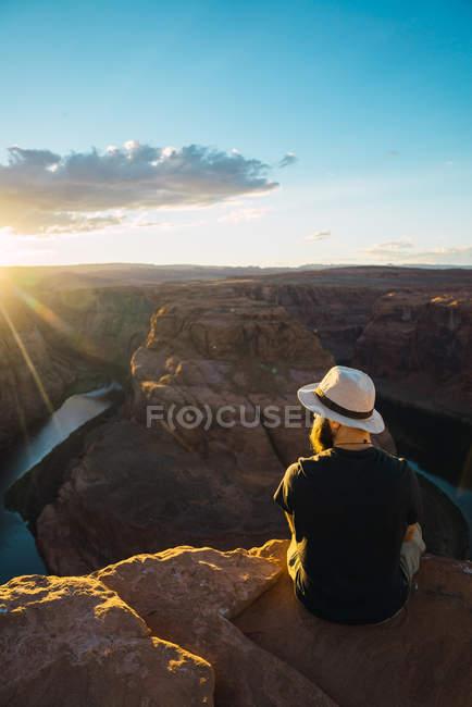 Vista trasera de un tipo barbudo mirando un hermoso cañón y un río tranquilo en un día soleado en la costa oeste de Estados Unidos - foto de stock