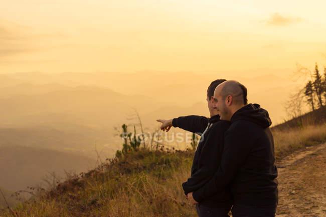 Pareja homosexual romántica abrazando en la ruta en las montañas al atardecer - foto de stock