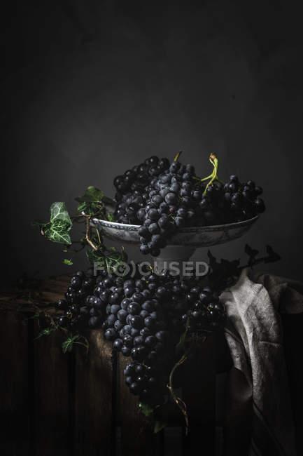 Ramo de uvas sobre placa de metal vintage sobre fondo oscuro - foto de stock