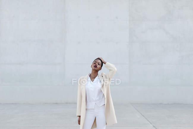 Короткошерстная модель в белом наряде, позирующая против серой стены — стоковое фото