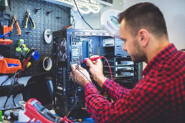 Focalizzato giovane uomo riparazione PC sul posto di lavoro — Foto stock