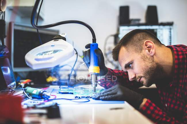 Focused man repairing motherboard with solder at workplace — Stock Photo