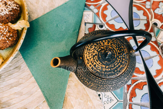 Розташування чайника біля тарілки з різними закусками їжі і серветкою за столом у кафе на розмитому фоні. — стокове фото