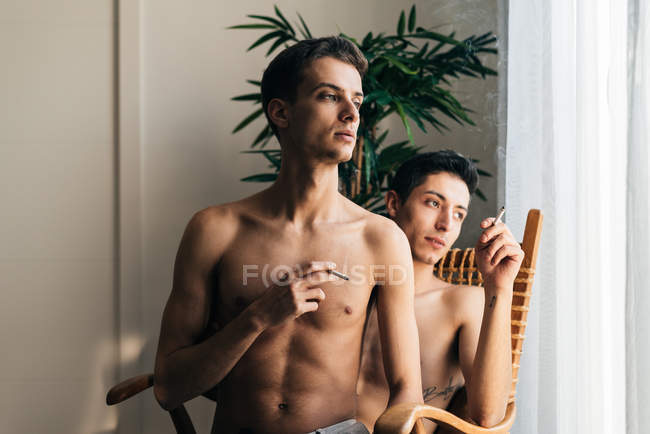 Stylish shirtless gay couple posing in front of the camera sitting in a chair smoking cigarette — Stock Photo