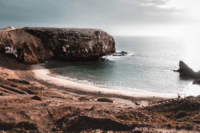 Picturesque view of cliff on coast near sea and cloudy sky in Lanzarote, Canary Islands, Spain — Stock Photo