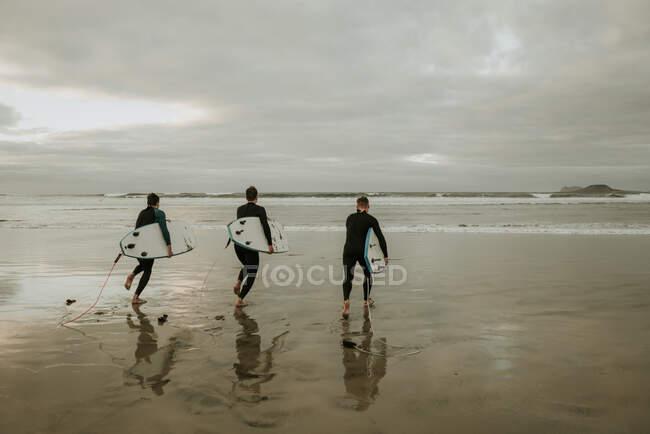 People with surfboard walking near sea — Stock Photo