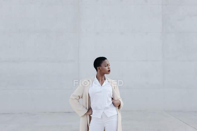 Mode à poil court modèle en tenue blanche posant contre le mur gris — Photo de stock