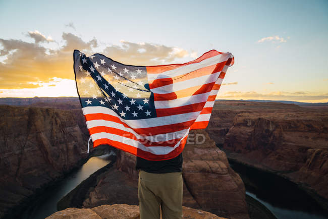 Back view of man with waving USA flag standing near beautiful canyon against sunset sky on West Coast — Stock Photo