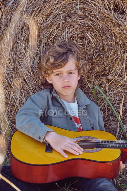 Netter Junge spielt Akustikgitarre und singt, während er an einem sonnigen Tag auf dem Land in der Nähe einer riesigen Rolle trockenem Heu sitzt — Stockfoto