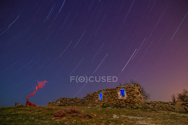 Long exposure of amazing sky with stars in evening and aged rock construction on hill — Stock Photo