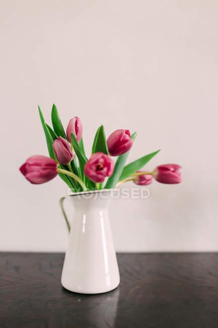Strauß frischer rosa Tulpen in Vase auf grauem Tisch — Stockfoto