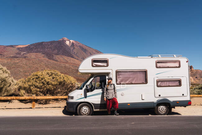 Guy near mobile house parked on asphalt route near picturesque view of blue heaven and mountain Teide in Tenerife, Canary Islands, Spain — Stock Photo