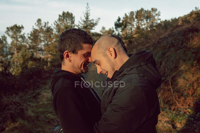 Side view of cheerful homosexual couple embracing on route in forest in sunny day — Stock Photo